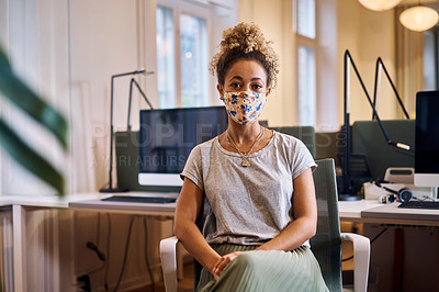 Buy stock photo Cropped portrait of an attractive young businesswoman sitting in her office while wearing a mask