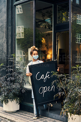 Buy stock photo Shot of a masked young woman displaying an open sign on the sidewalk of her cafe