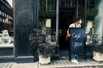 Buy stock photo Shot of a masked young man displaying an open sign on the sidewalk of his cafe