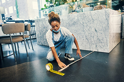 Buy stock photo Shot of a young woman measuring the required space for social distancing in her cafe