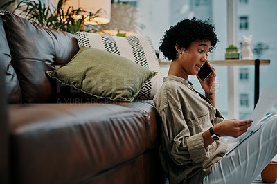 Buy stock photo Shot of a young woman talking on her cellphone while looking at paperwork