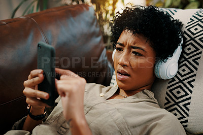 Buy stock photo Shot of a young woman wearing headphones while using her cellphone at home