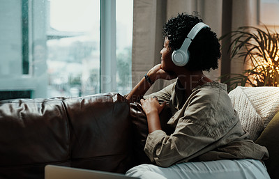 Buy stock photo Shot of a young woman wearing headphones while looking out her living room window