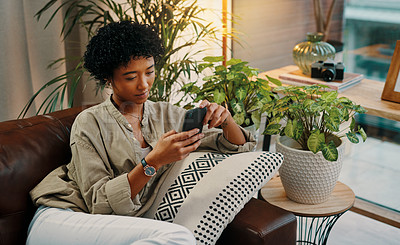 Buy stock photo Shot of a beautiful young woman using her cellphone while sitting at home