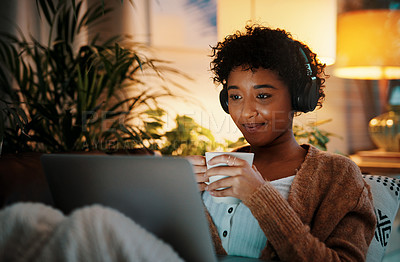 Buy stock photo Shot of a woman wearing headphones and drinking coffee while watching something on her laptop at night