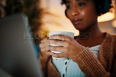 Buy stock photo Shot of a young woman holding a mug while watching something on her laptop