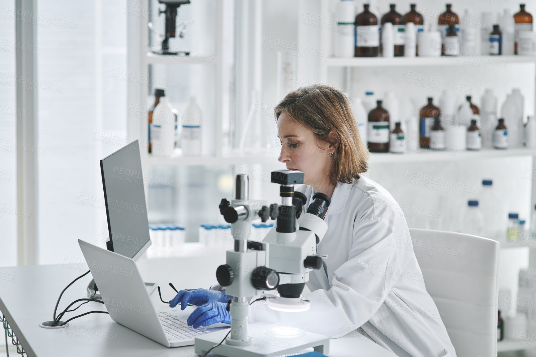 Buy stock photo Shot of mature scientist working on a laptop in a lab