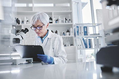 Buy stock photo Shot of a mature scientist writing notes while working in a lab