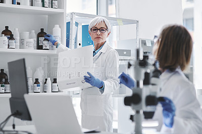 Buy stock photo Shot of a mature scientist working with chemicals from a shelf in a lab with her colleague