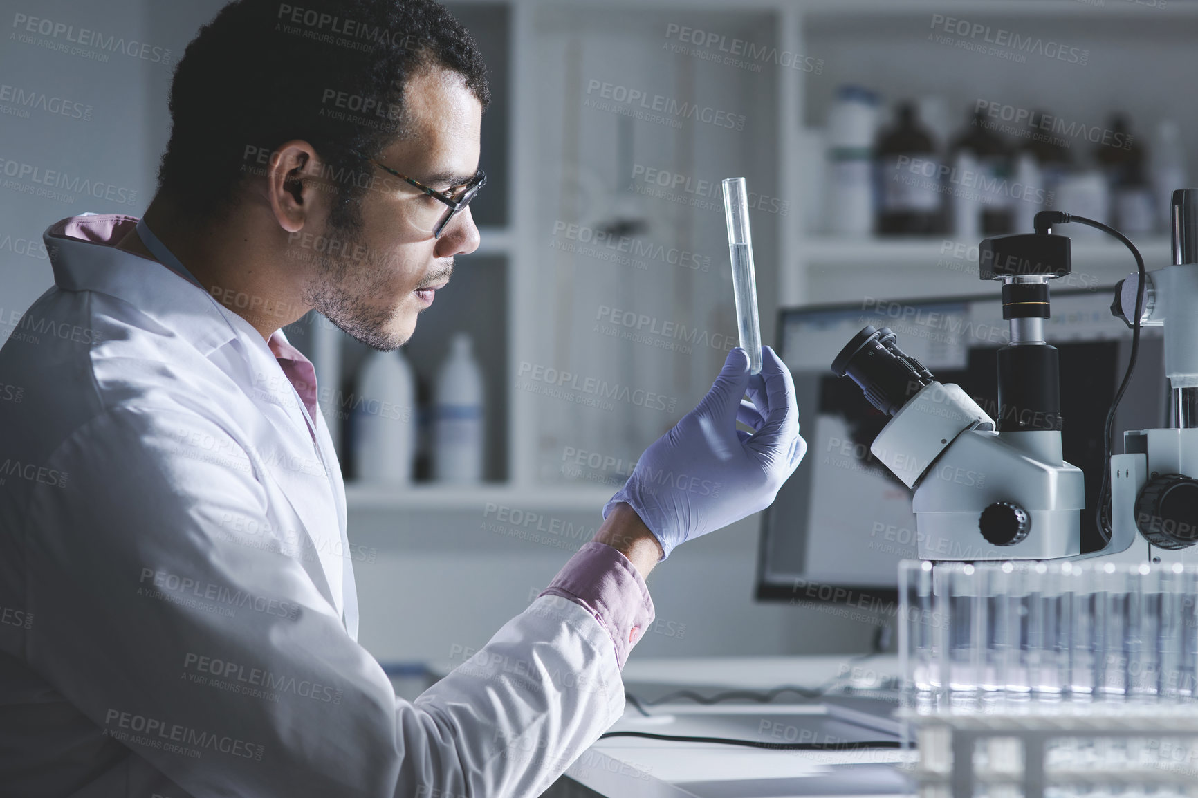 Buy stock photo Shot of a young scientist analysing samples in a test tube in a lab