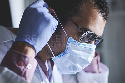 Buy stock photo Shot of a young scientist wearing a protective mask and gloves in a lab