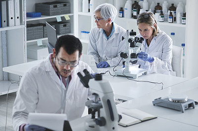 Buy stock photo Shot of a group of scientists working in a lab