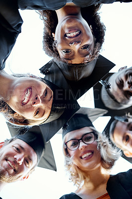 Buy stock photo Portrait of a group of students putting their heads together in a huddle on graduation day