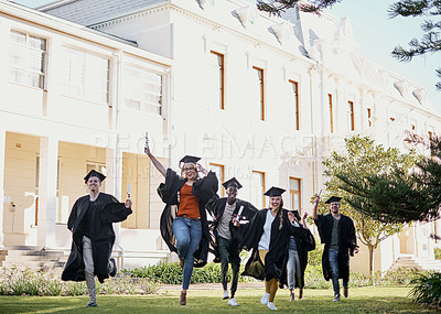 Buy stock photo Shot of a group of students running together in a row on graduation day