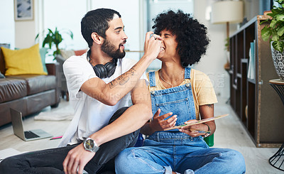 Buy stock photo Shot of a young couple enjoying themselves while painting at home