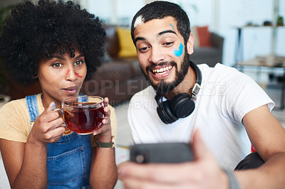 Buy stock photo Shot of a man holding up his cellphone while sitting at home with his girlfriend