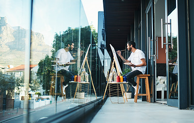 Buy stock photo Shot of a man doing a painting while sitting on the balcony at home