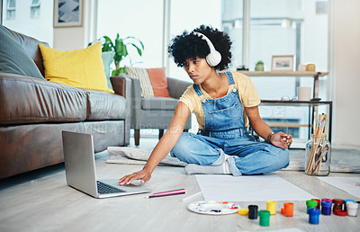 Buy stock photo Shot of a young woman using her laptop while sitting at home with paint and a blank canvas