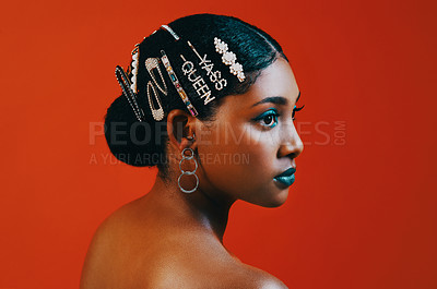 Buy stock photo Studio shot of a beautiful young woman wearing hair clips against a orange background