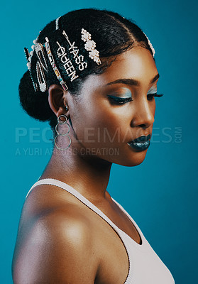 Buy stock photo Studio shot of a beautiful young woman wearing hair clips against a blue background