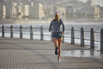 Buy stock photo Rearview shot of a sporty young woman running along a promenade