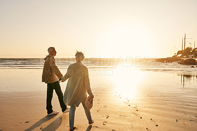 Buy stock photo Rearview shot of a senior couple walking along the beach