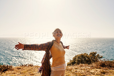 Buy stock photo Shot of a senior woman with her arms outstretched at the beach