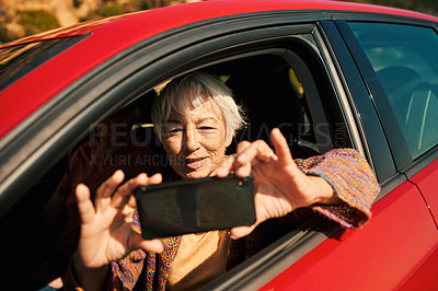 Buy stock photo Shot of a senior woman taking photos on a cellphone while sitting in a car