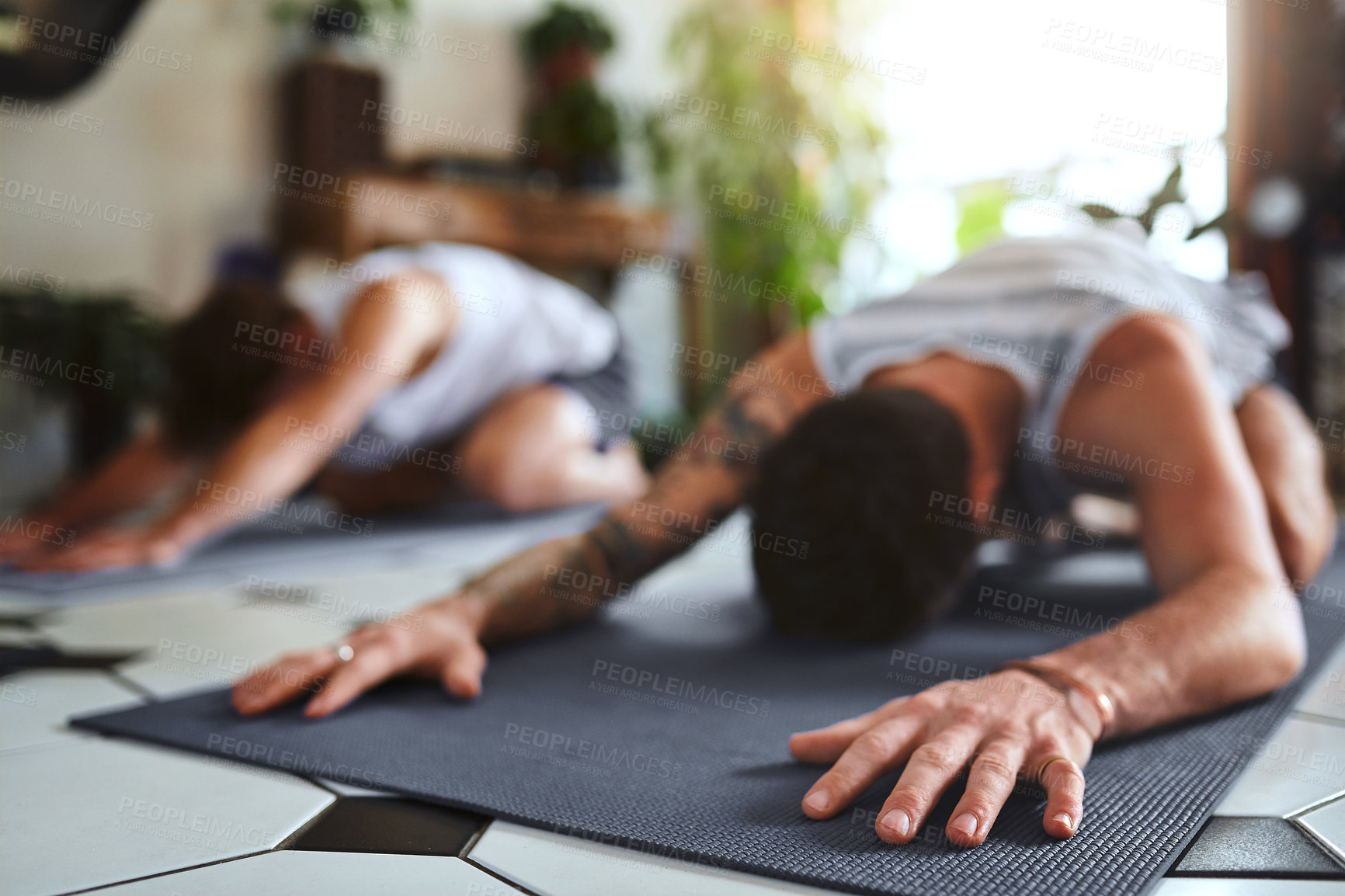 Buy stock photo Shot of two men going through a yoga routine at home