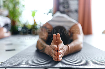 Buy stock photo Shot of a young man going through a yoga routine at home