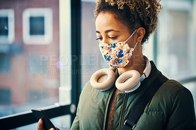 Buy stock photo Shot of a masked young woman using a smartphone while travelling through a subway station