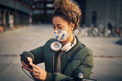 Buy stock photo Shot of a masked young woman using a smartphone while riding her bicycle through the city