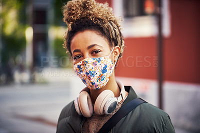Buy stock photo Shot of a young woman wearing a mask while out and about in the city