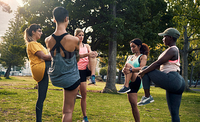 Buy stock photo Shot of a group of young women exercising together in a park