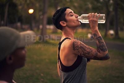 Buy stock photo Shot of a young woman drinking water during a workout with friends at the park