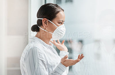 Buy stock photo Shot of a masked young businesswoman looking out of a window and talking to someone at work