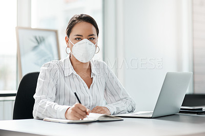 Buy stock photo Shot of a masked young businesswoman working at her desk in a modern office