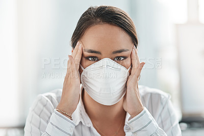 Buy stock photo Shot of a masked young businesswoman looking stressed while working in a modern office