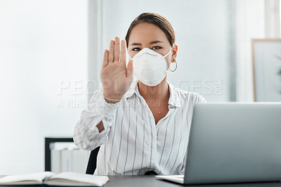 Buy stock photo Shot of a masked young businesswoman gesturing to stay away while working at her desk in a modern office
