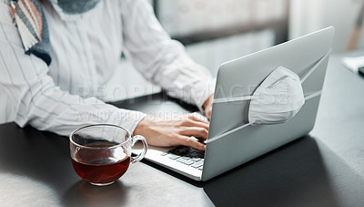 Buy stock photo Cropped shot of a businesswoman using a laptop with a mask wrapped around it and having herbal tea