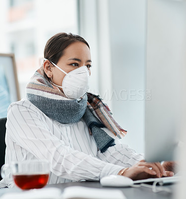 Buy stock photo Shot of a masked young businesswoman using a computer in a modern office