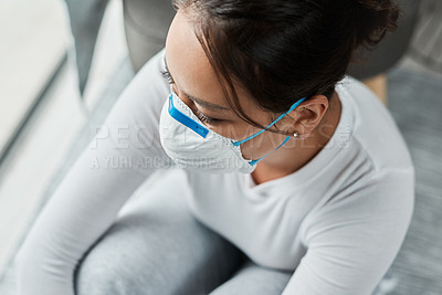 Buy stock photo Shot of a woman wearing a mask while sitting at home