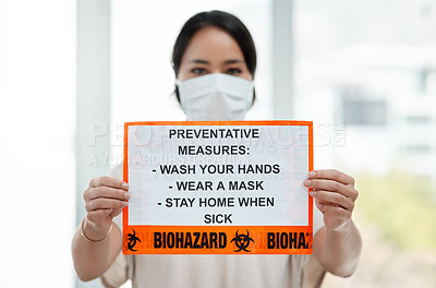 Buy stock photo Shot of a woman holding up a sign with a list of COVID-19 prevention measures
