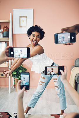 Buy stock photo Shot of a beautiful young woman having her picture taken on multiple phones