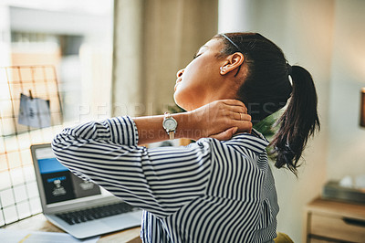 Buy stock photo Shot of a young woman rubbing her neck while working from home