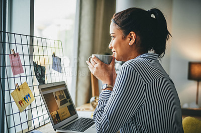 Buy stock photo Shot of a young woman drinking coffee while working from home
