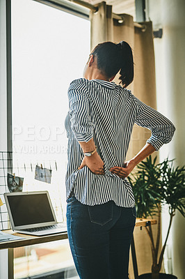 Buy stock photo Rearview shot of a young woman suffering with back pain while working from home
