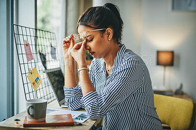 Buy stock photo Shot of a young woman looking stressed out while working from home