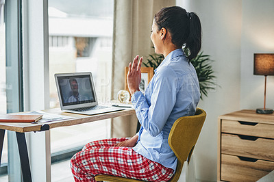 Buy stock photo Shot of a young woman having a video call with her colleague while working from home