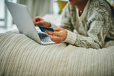 Buy stock photo Shot of an unrecognisable woman using a laptop and credit card on the bed at home